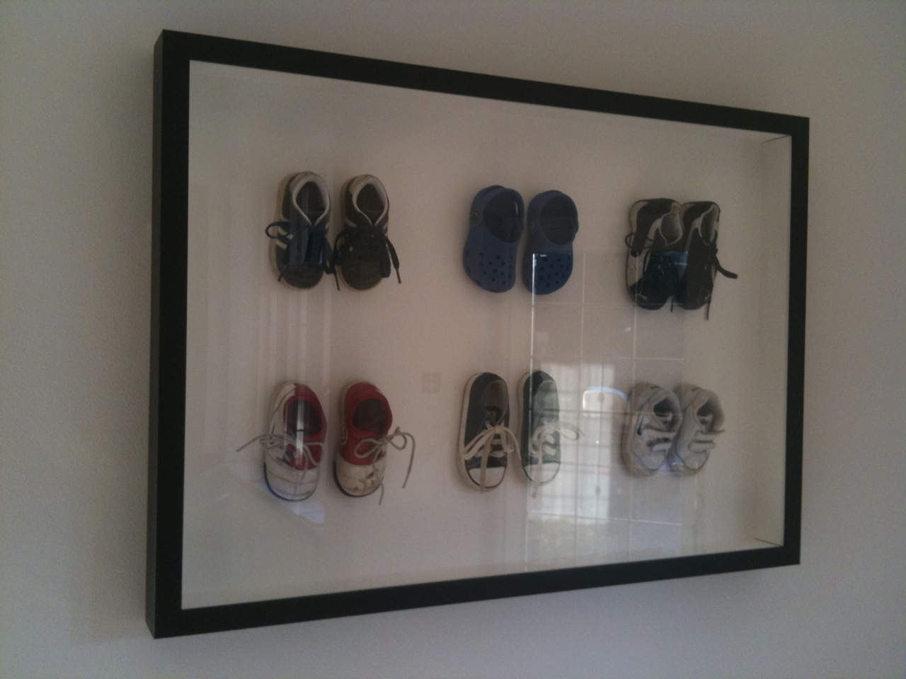 Collection of children's shoes framed by Bespoke Framing